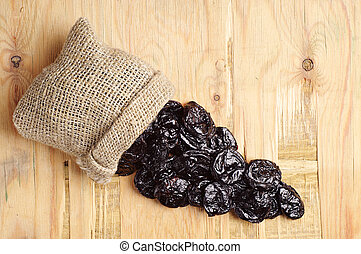 Prunes in small sack on wooden background. Top view