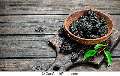 Prunes with green leaves in the bowl.