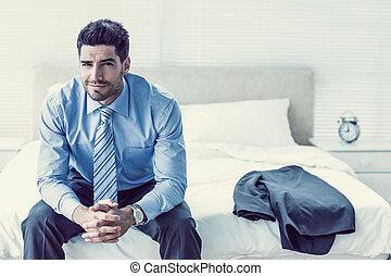 przystojny, biznesmen, posiedzenie na łóżku, aparat fotograficzny przeglądnięcia