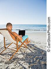 przystojny, laptop, jego, ogniskowany, pracujący, człowiek