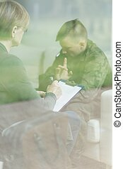 Psychiatrist listening male soldier