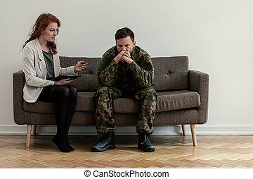 Psychiatrist talking to her angry patient while sitting on a sofa