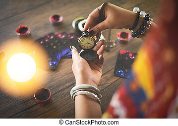 Psychic readings and clairvoyance concept - Crystal ball fortune teller with hands hold retro pocket watch and Tarot cards reading divination