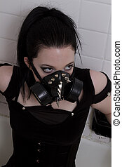crazy looking teenage girl wearing goth inspired clothes with black hair and gas mask in a tub