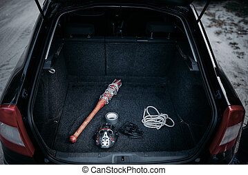 Psycho man instruments in opened car trunk, maniac. Hockey...