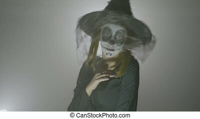 Psycho witch with hat and veil moving in a scary way and...