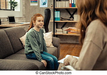 Cute positive girl looking at her therapist