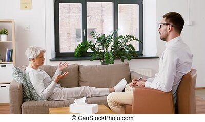 psychologist giving glass of water to senior woman -...