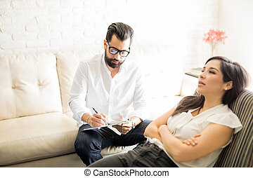 Psychologist making notes during therapy session with patient