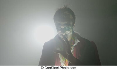 Psychopath male joker laughing crazy evil and frightening the camera on halloween