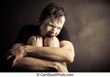Psychotic and angry teen chews his knees drawing blood while seated against dark wall