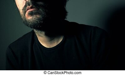 Psychotic bearded man with mental problems, low key portrait in dark room