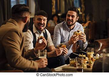 Pub Food And Drinks - Three men are sitting together in a...