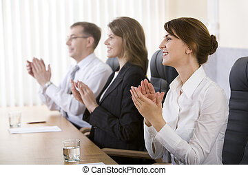 Successful applauding young people sitting at the table in black comfortable chairs