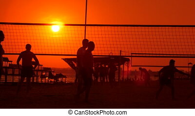 Public beach with a volleyball courts and players silhouettes in the sun