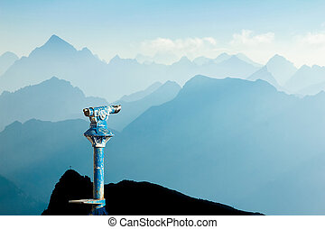 Public binoculars and Mountain Silhouettes at Sunrise. Foresight and vision for new business concepts and creative ideas. Alps, Allgau, Bavaria, Germany.