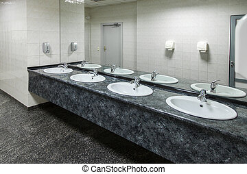 Public empty restroom - Row of wash basins with mirrors in...