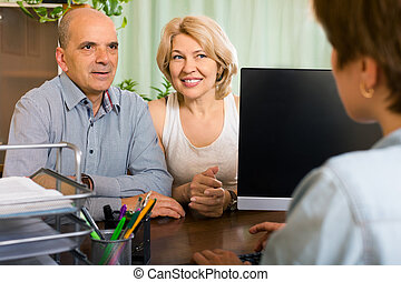 Public notary helping happy senior couple to make a will in...