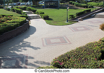 Public park with walkways, gardens and a seating area
