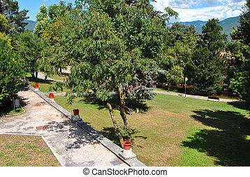 public park with grass trees and benches