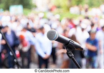 Public speaking - Microphone in focus against blurred...