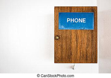 Public telephone on white wall
