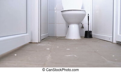 Public toilet cubicles. The camera moves smoothly from below between the white cabins of the toilet