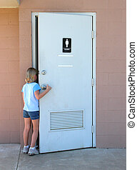 Public Toilet - Young girl entering a public toilet. Main...