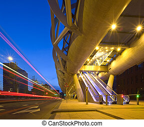A city bus driving past an elevated tram viaduct, with automated escalators leading up to the platform A stich of two images