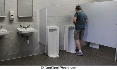 public urinal - mature man using the urinal in a public...