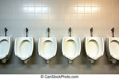 Public Urinals - A row of urinals in tiled wall in a public...