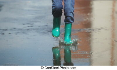 Puddle fun - Girl running, jumping and splashing in the...