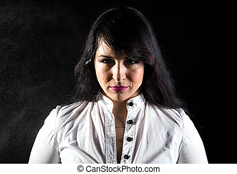 Pudgy wet woman in shadows on black background