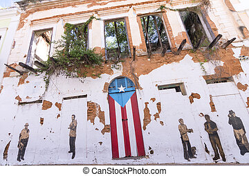 Exterior of old dilapidated building featuring paintings of famous Puerto Ricans and a door painted like the Puerto Rican flag in Old San Juan