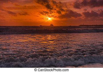 puesta sol roja, en la playa