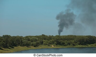 Puff Of Black Smoke In Blue Sky Above Forest.