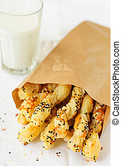Puff Pastry Sticks in a Paper Bag with a Glass of Milk, copy space for your text