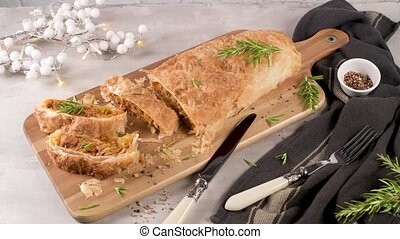 Puff pastry vegetable roll on kitchen decorated countertop.