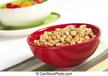 Puffed wheat cereal in red bowl with fruit salad in the background (Selective Focus, Focus on the middle of the cereals)