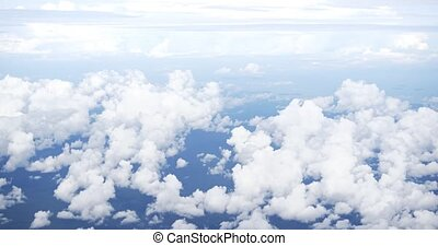 Puffy, cottony clouds billowing far below, taken from the passenger window of a commercial airliner in flight. Video 4k