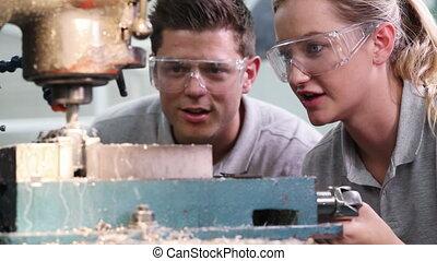 Pull Focus Shot Of Engineer Training Female Apprentice To...