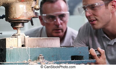 Pull Focus Shot Of Engineer Training Male Apprentice To Use...