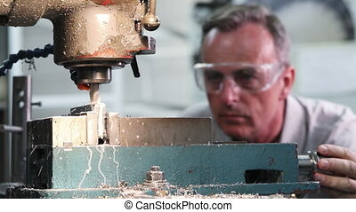 Pull Focus Shot Of Male Engineer Using Drill In Factory