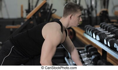 pull the dumbbell to the belt - Muscular man leaning on the...
