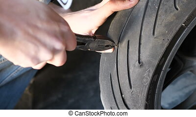 Pull the nail out of the tire of the motorcycle wheel using pliers
