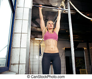Pull Up - Young adult fitness woman preparing to do pull ups...
