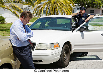 Embarassed looking businessman pulled over by the police. Focus is on the businessman.