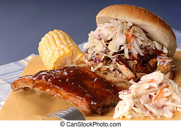 Pulled pork sandwich with cole slaw on it with ribs, corn and beans