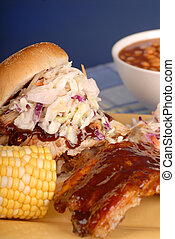Pulled pork sandwich with cole slaw, corn and beans
