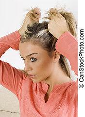 pulling hairn - portrait of a pretty blond female wearing ...